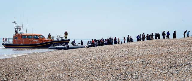 Pictured: People though to be migrants are watched over by the RNLI yesterday as they make their way up the beach