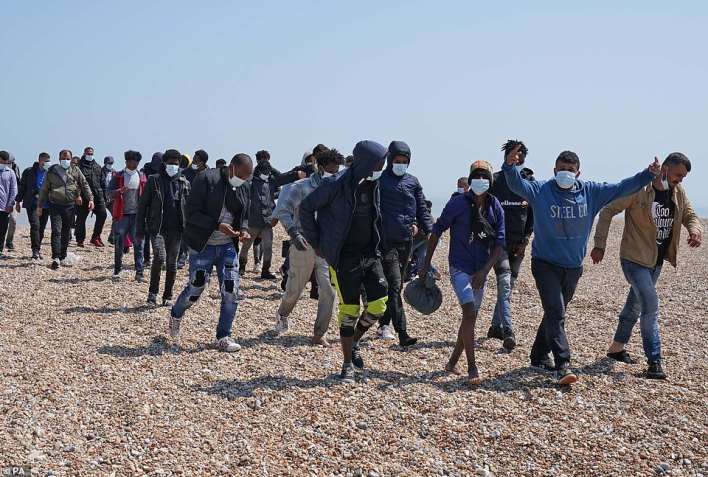Priti Patel agreed to give French border authorities £54m to help stop migrants crossing the Channel - as the total of arrivals in Britain this year hit 8,000. Pictured: Migrants are escorted from the beach at Dungeness, Kent, by Border Force officers