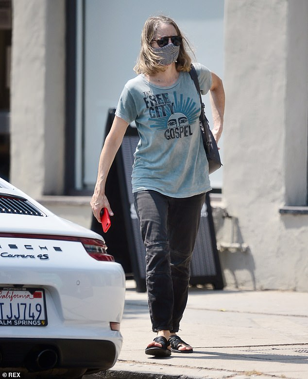 Chilled: Jodie Foster, 58, cut a casual figure in a blue graphic tee and black jeans as she stepped out in Los Angeles after getting her nails done on Wednesday