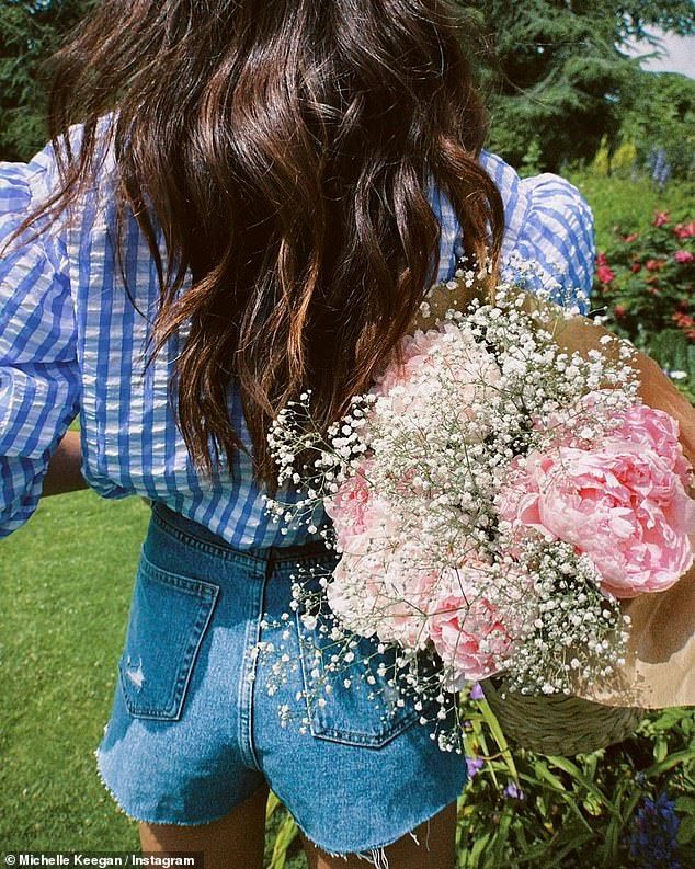 Floral queen: The actress, 34, made the most of the balmy UK temperatures as she explored a country garden