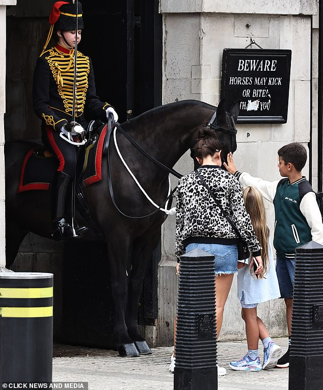 Stroking: Taylor and Sofia gently stroke one of the horses at the Queen's Residence