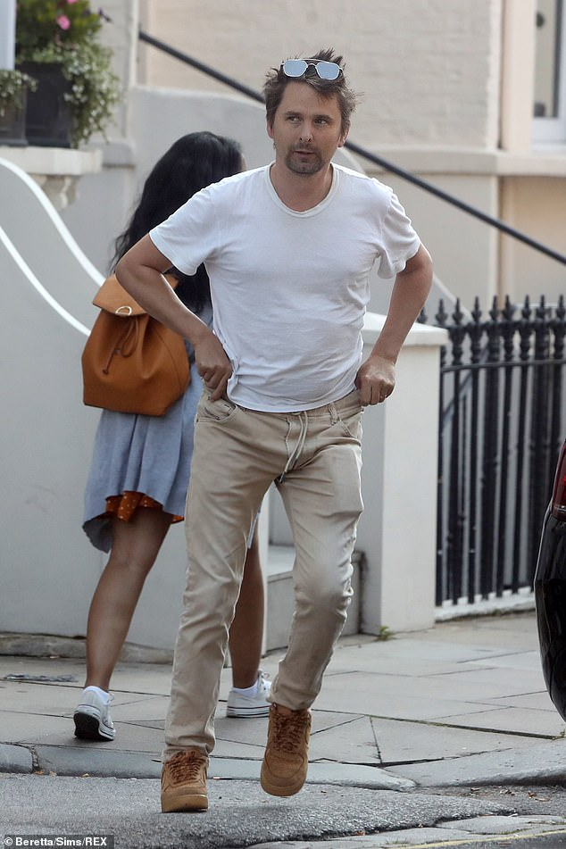 Understated look: The Muse star paired the white T-shirt with stone-colored chinos and brown suede shoes