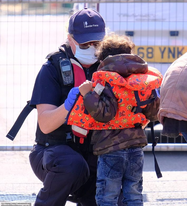 A Border Force official is seen putting a children's lifejacket on a child migrant at Dover Marina in Kent