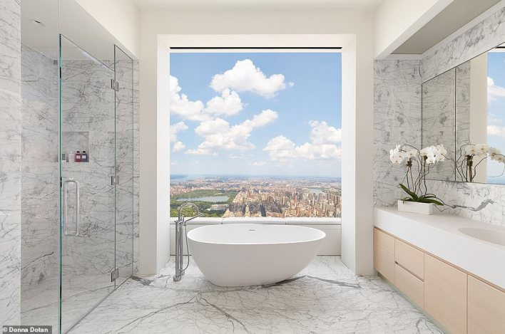 A large free-standing bath is located in the center of the master bathroom in a similar penthouse condominium