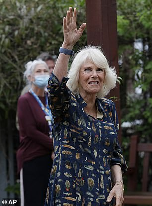The Duchess of Cornwall waves to the looking staff as she visits the hospital gardens