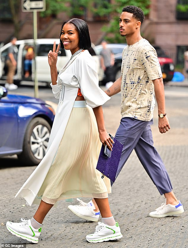 Stylish star: The actress wore a flowing white dress and a pair of lighter sneakers with bright green stripes