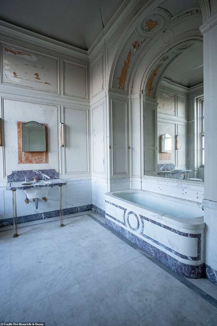 The bathroom is fitted with a grand stone bath and plush sink fixture, but missing paint patches on the walls betray the fact that the stately home has long been empty