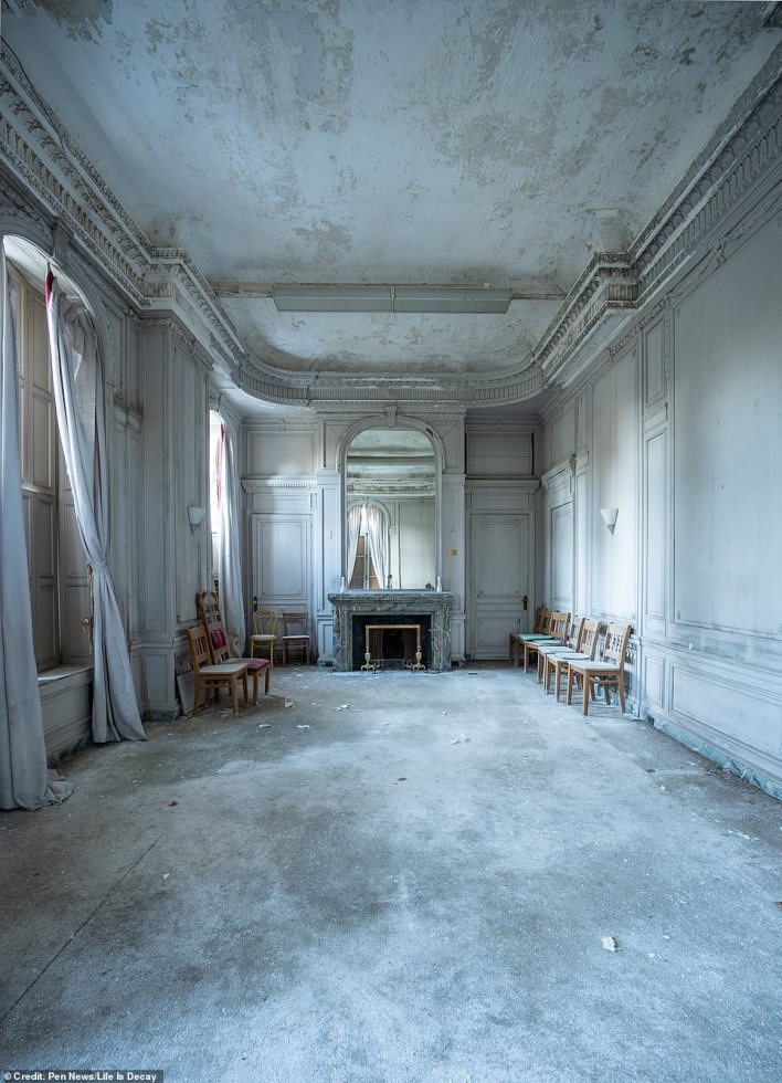 The former breakfast room is now mostly empty, besides a few cheap wooden chairs and a large mirror looming above the fireplace