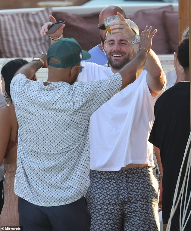 Smiling: Luke put on an animated display as he greeted one of his friends at the party on the Greek island of Mykonos