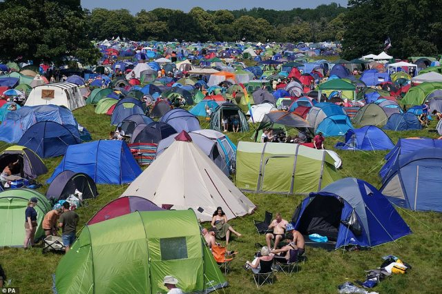 Festivalgoers in the sunshine at the campsite at the Latitude festival at Henham Park in Southwold, Suffolk, today