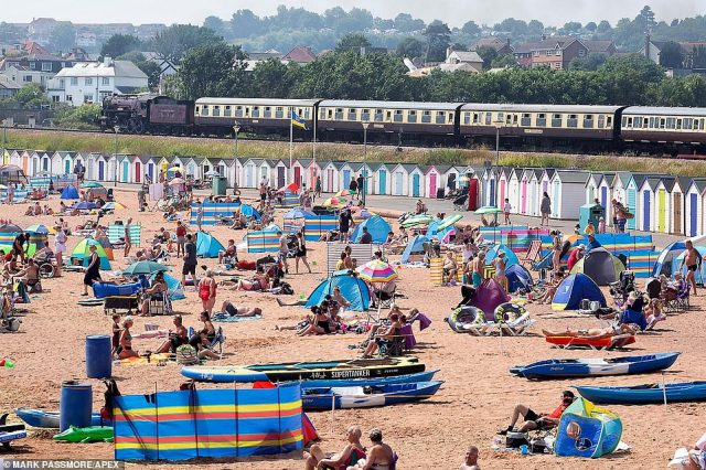 A steam train passes as sunseekers flock to the beach at Goodrington in Devon this afternoon