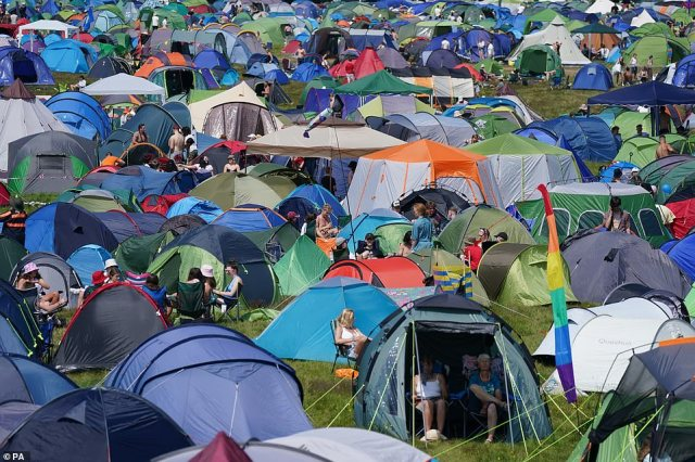 Festivalgoers sit amongst their tents at the Latitude festival in Henham Park, Southwold, Suffolk this afternoon