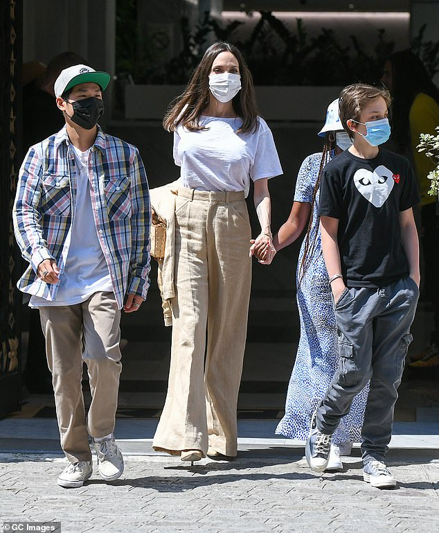 Casual: Shiloh, meanwhile, wore a black shirt with gray cargo pants and Pax wore a colorful plaid shirt over a white top and khaki chinos