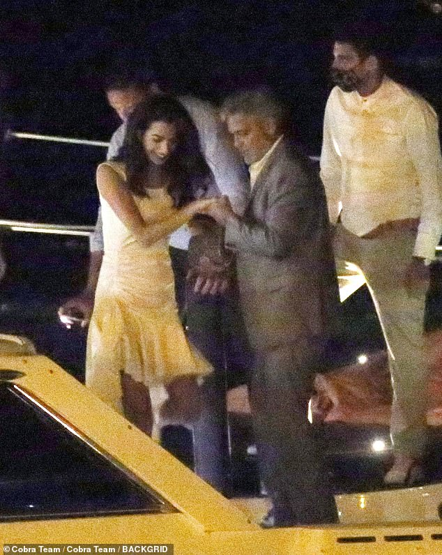 Helping hand: George Clooney was the perfect gentleman when he helped glamorous woman Amal board a boat after dinner with her family in Lake Como on Wednesday