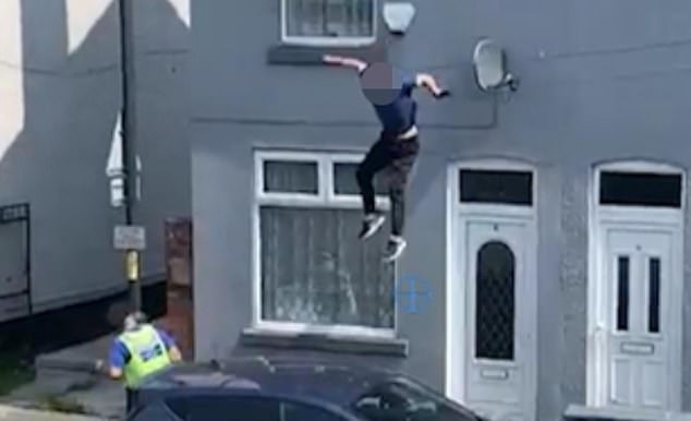 The man (pictured), who is currently unnamed, was standing atop a house surrounded by police in Walsall, near Birmingham, when he slipped