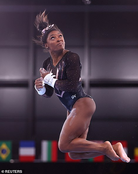 Simone Biles practices on the uneven bars on Thursday