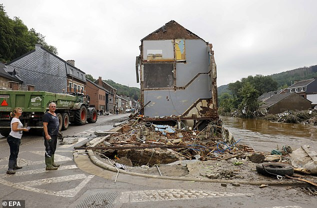 Residents look at damage caused by days of torrential rain and flooding in Pepinster, Belgium on Saturday