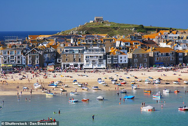 Cornwall Council is also asking people to buy and pack Covid testing kits before travelling so they can regularly use them while there (pictured: the seaside village of St Ives)