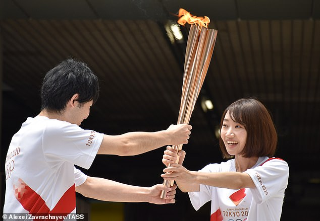Two torch-bearers past the Olympic flame during an event that replaces the traditional relay due to Covid restrictions in Japan