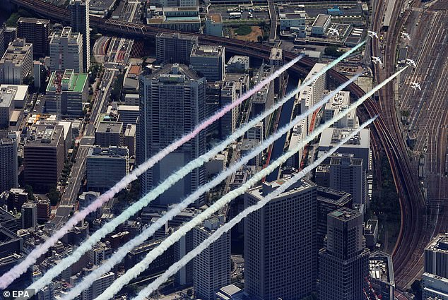 Blue Impulse display jets release coloured smoke over Tokyo just hours before the main Opening Ceremony is due to take place