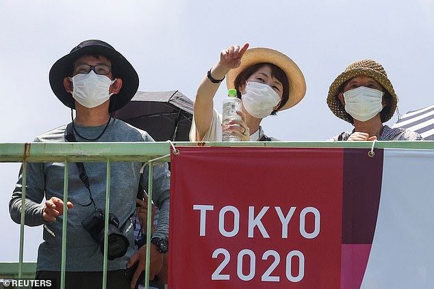 People excited about the arrival of the Games stand outside the National Stadium before the opening of the Tokyo 2020 Olympics