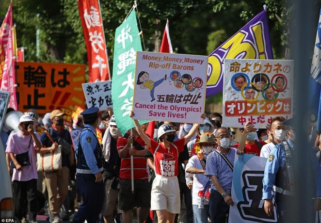 Protesters gather outside Tokyo's main Olympic stadium carrying banners that demand the event is called off, just hours before it goes ahead