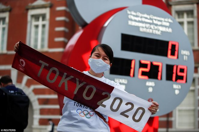 A giant digital clock in Tokyo counts down to the start of the opening ceremony as fans gather in front of it