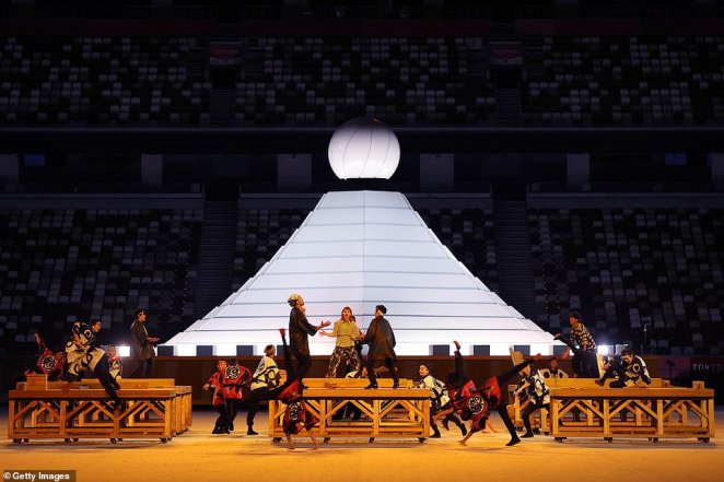 Performers dance as the Olympic Cauldron is seen during the Opening Ceremony of the Tokyo 2020 Olympic Games