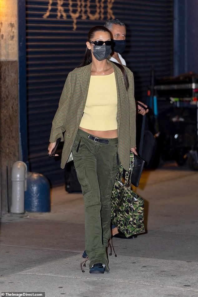 More concealed: Hadid later wore a green, red and yellow houndstooth blazer over the cropped top.  She wore a camouflage tote bag that completed her army-inspired look