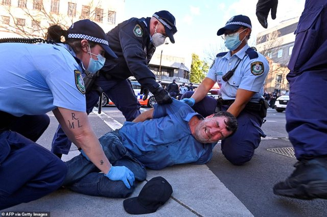 Another man is seen on the ground after being tackled by police in Sydney as thousands gathered to demonstrate against the city's lockdowns