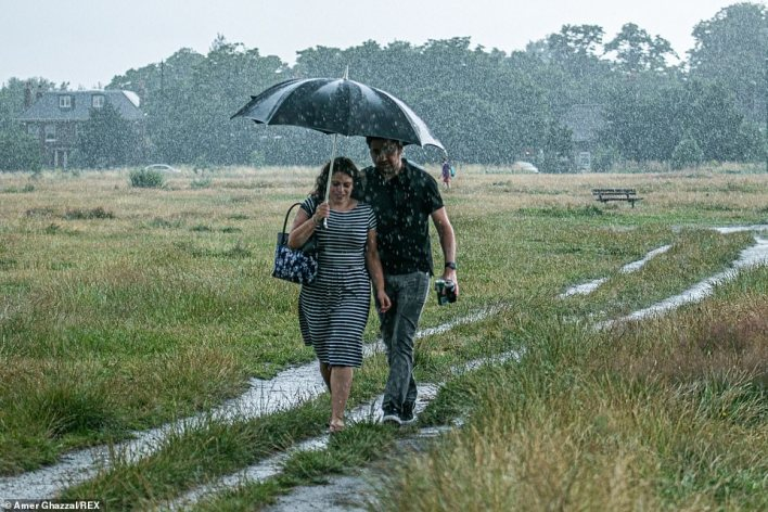 Two people shelter under the same umbrella as the walk through the grass at Wimbledon Common on the rainy Sunday afternoon