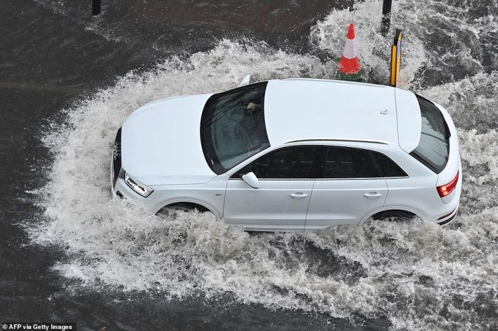 A car drives through water on a flooded road in The Nine Elms district on London on Sunday following hours of heavy rain in the capital