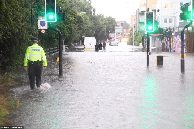 The River Roding in East London burst its banks yesterday afternoon after torrential downpours. Pictured: Chigwell Road