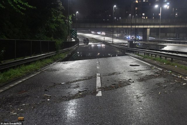 Pictured: The A406 Southend Road remained closed into this morning as floodwater submerged both sides of the road