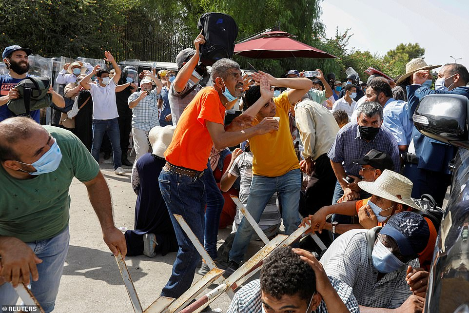Ennahda supporters take cover from stones thrown at them by supporters of President Kais Saied outside the parliament on Monday