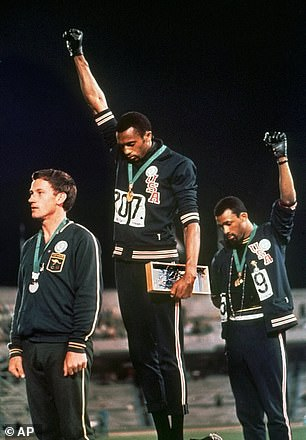 In this 1968 file photo extending gloved hands skyward in racial protest, Tommie Smith, center, and John Carlos stare downward during the playing of anthem after Smith received the gold and Carlos the bronze for the 200 meter run at the Summer Olympic Games in Mexico City. Australian silver medalist Peter Norman is at left