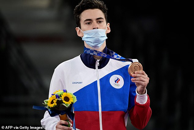 The Russian flag is nowhere to be seen, having been banned from any Olympic venue outside the Olympic Village, but its colours feature on the team's kit. Pictured: Mikhail Artamonov wins bronze in the men's 58kg Taekwondo