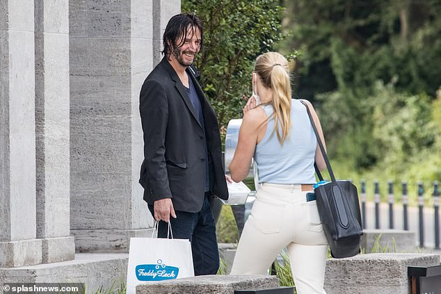 Smile:Keanu Reeves looked in great spirits as he flashed a beaming smile at a female production assistant while leaving his Berlin hotel on Monday
