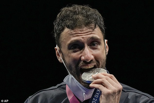 Team Italy's Luigui Samele, 34, takes a bite of the silver medal he won in the men's individual final Sabre competition