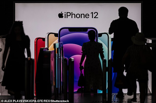 People enter the subway in front of a Apple's iPhone 12 advertisement, in Shanghai, China on July 9