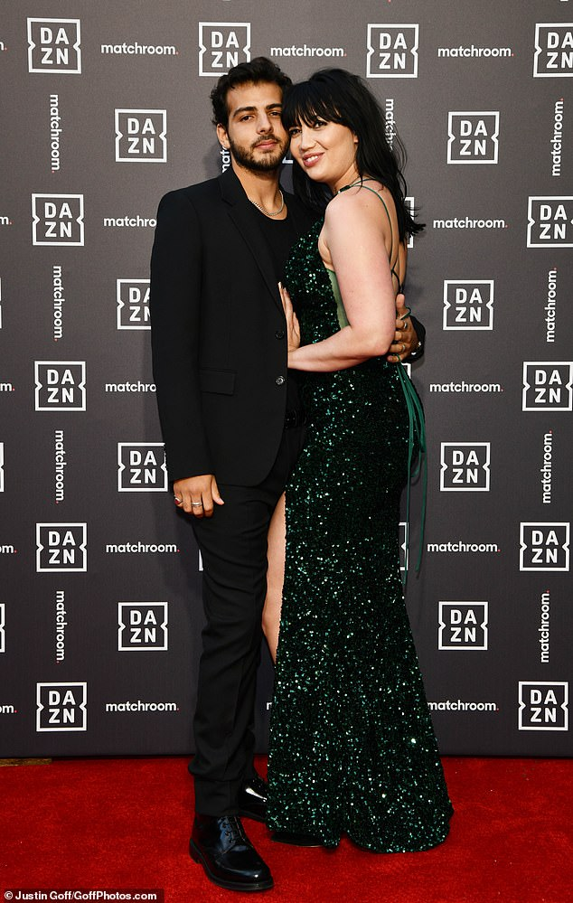 Loved-up: Daisy's boyfriend opted for an all black ensemble in a T-shirt, blazer, slacks and shiny loafers as they cosied up on the red carpet.