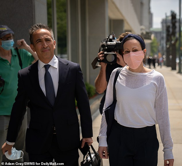 Salzman's daughter Lauren Salzman, 45, was also part of the cult and was spared jail time in July. Lauren is seen leaving court flanked by her lawyer