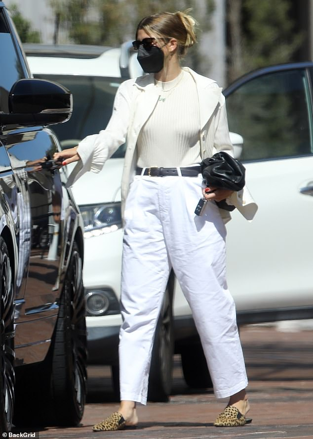 Summer color palette:The slender blonde rocked a pair of baggy white trousers that she secured with a black belt and a white knit shirt