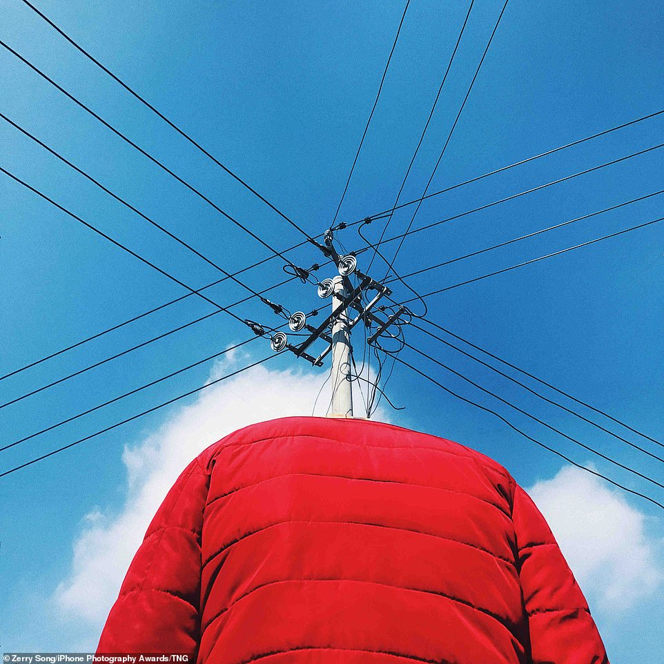 New Clothes for the Pole: A red puffer jacket is angled in such a way to make it look like a communications pylon is coming out of the coat, forming a head, before cables jet off in four directions. The composition was captured byZerry Song inLuoyang, Henan, China