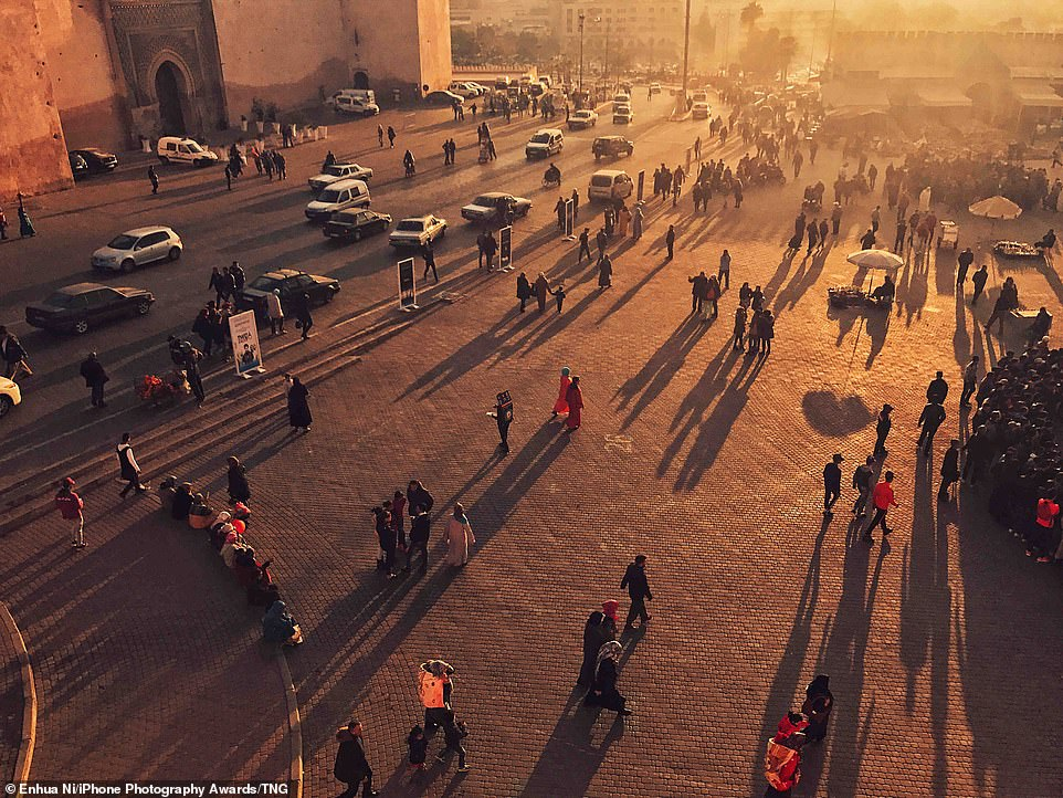 Dusk: As the sun sets over Meknes, Morocco, people are seen casting long shadows as they mill about inLahdim Square, a large gathering place known for itsfood sellers, market stalls & imperial Bab Mansour gate inEnhua Ni's photograph
