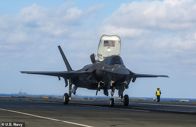 An American F-35 stealth fighter lands on the deck of HMS Queen Elizabeth during joint operations in the South China Sea