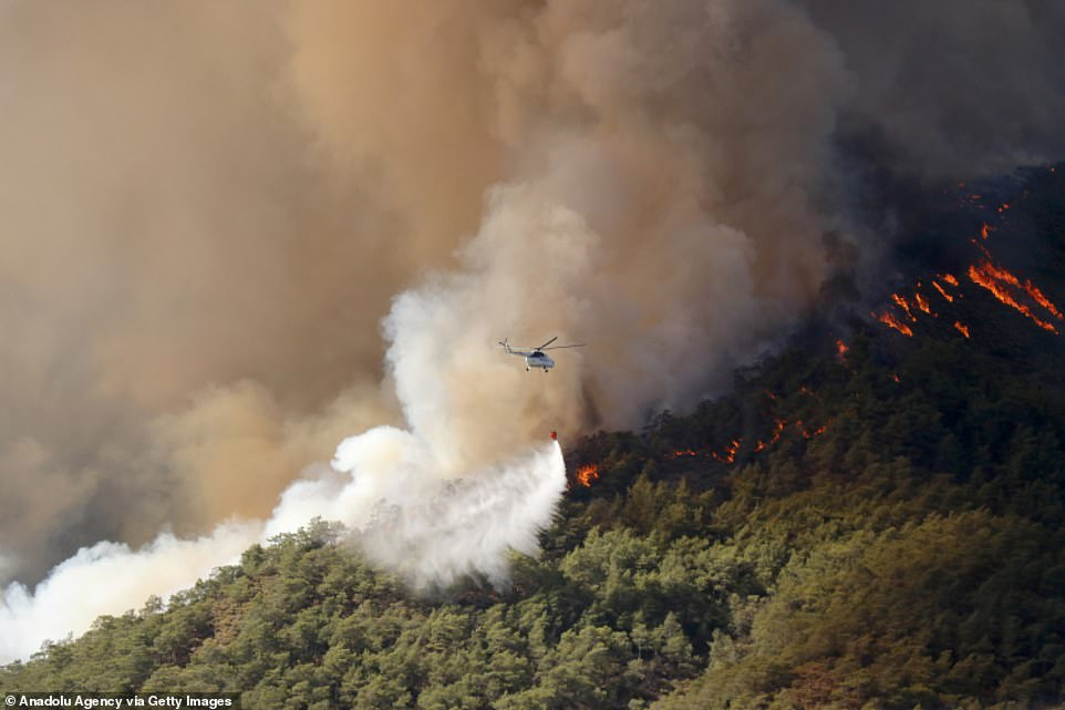 A helicopter flies over Mugla in Turkey's Marmaris district on Thursday as efforts to extinguish forest fires in the region continued
