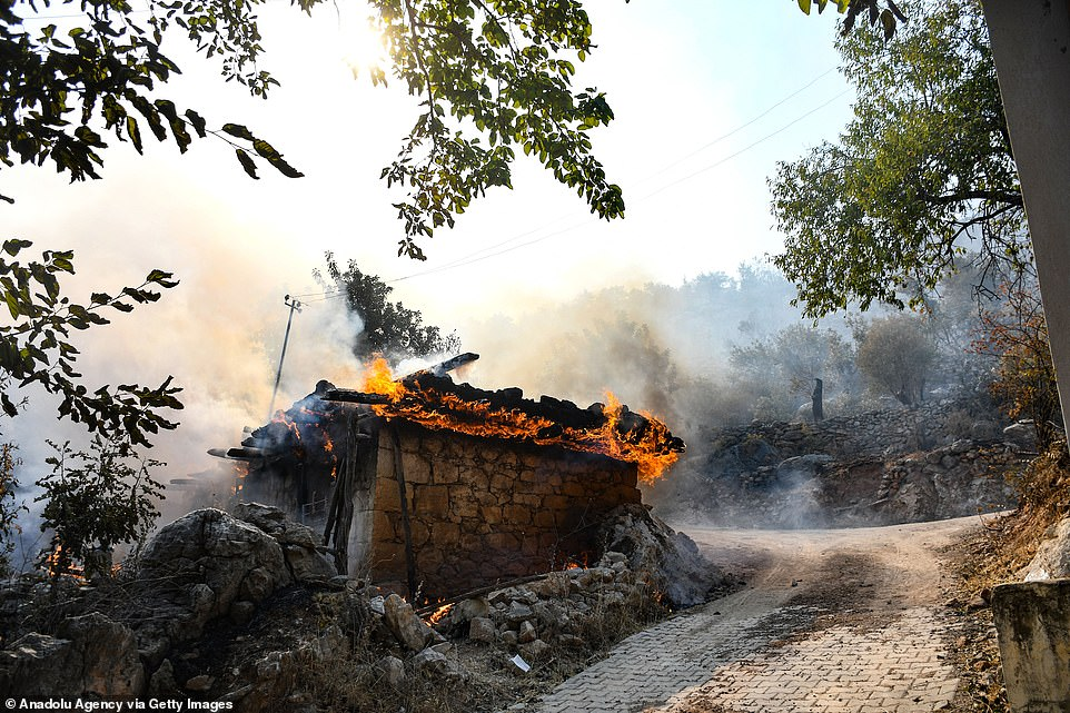 A damaged house in Aydincik, near Mersin in Turkey, was engulfed in flames on Thursday as forest fires swept the region fanned by strong winds
