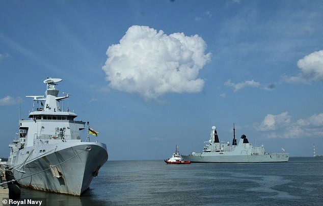 HMS Defender is shown at anchor alongside a ship of the Brunei navy during a visit to port as the UK's carrier group carries out exercises in the South China Sea