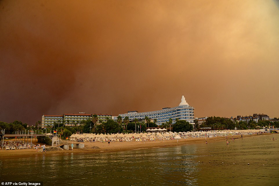 Dark smoke drifts over a hotel complex during a massive forest fire which engulfed a Mediterranean resort region on Thursday